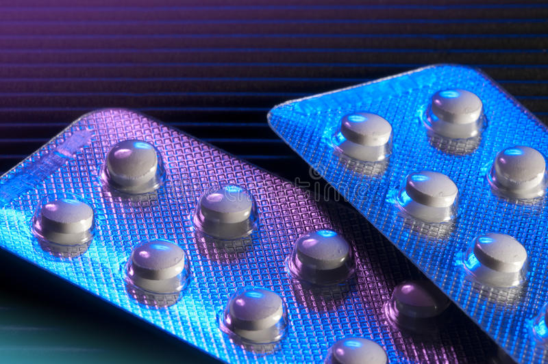 Multiple pills in foil. Packaged pills in foil lit by blue and purple lights on black background royalty free stock photo