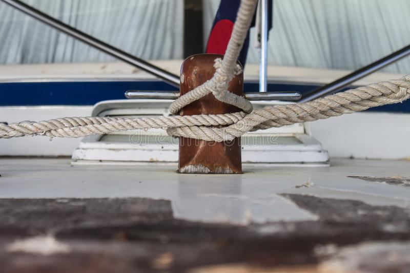 Multiple ropes tied to wooden cleat on vintage wooden boat royalty free stock photography