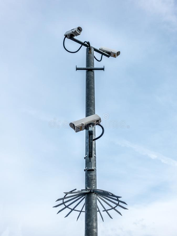 Multiple security cameras on a pole. Multiple security cameras looking down from a pole with the sky in the background royalty free stock photos