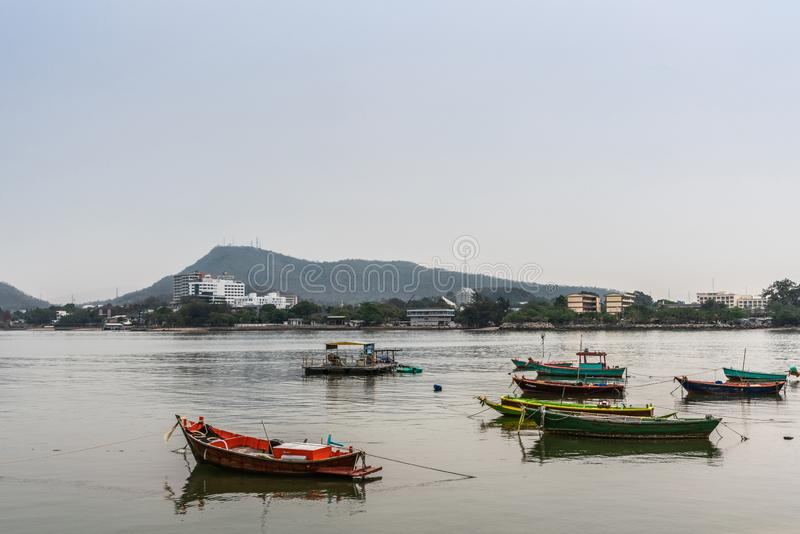 Multiple small fishing vessels off beach of Si Racha, Thailand. Si Racha, Thailand - March 16, 2019: Multiple small fishing vessels on flat gray water just off royalty free stock image