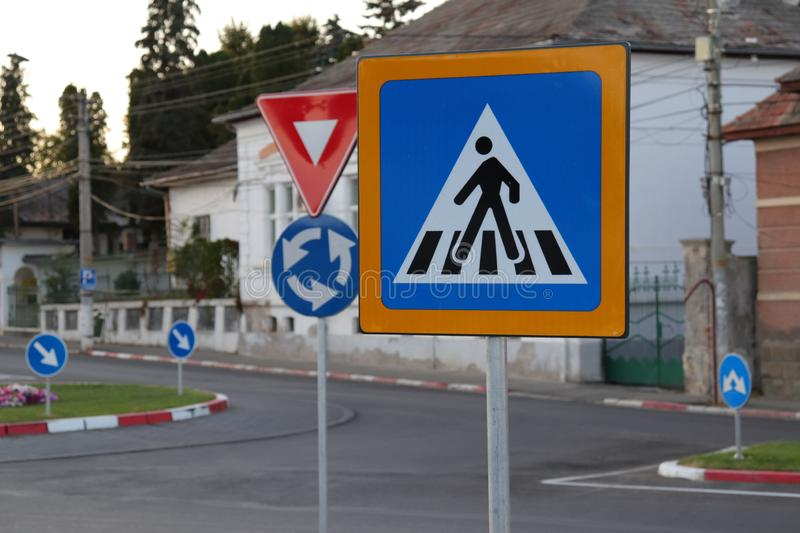 Multiple street signs in a roundabout, a pedestrian crossing, right of way in an empty intersection royalty free stock image