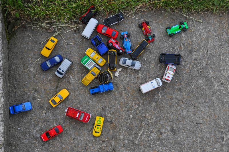 Multiple toy cars on play ground. Multiple colorful toy cars made from metal and plastic on play ground asphalt stock image