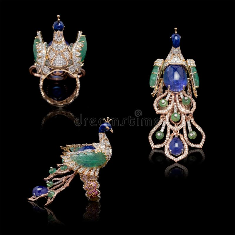Multiple view of Close up of three beautiful peacock-shaped gold diamond ring. On black background royalty free stock photos