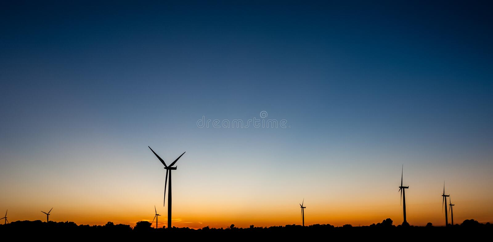 Multiple wind turbine outlines on orange and blue sky. Black silhouettes of several wind turbines against orange and blue sky at dusk stock images