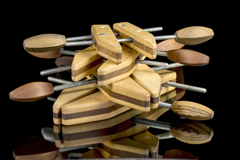 Multiple wood clamps on a reflective surface stock photos