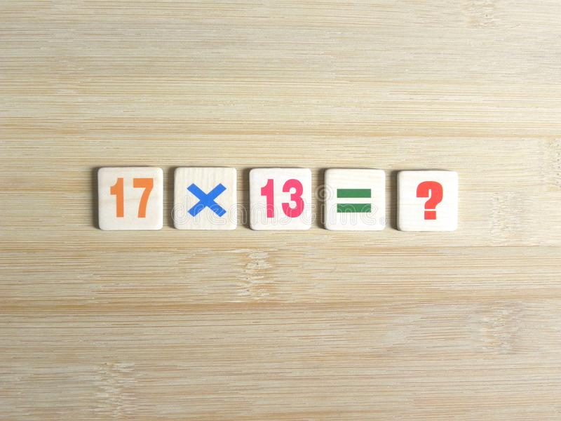 Multiply two numbers. Multiplication of two whole numbers 17x13=? on wood background stock photography