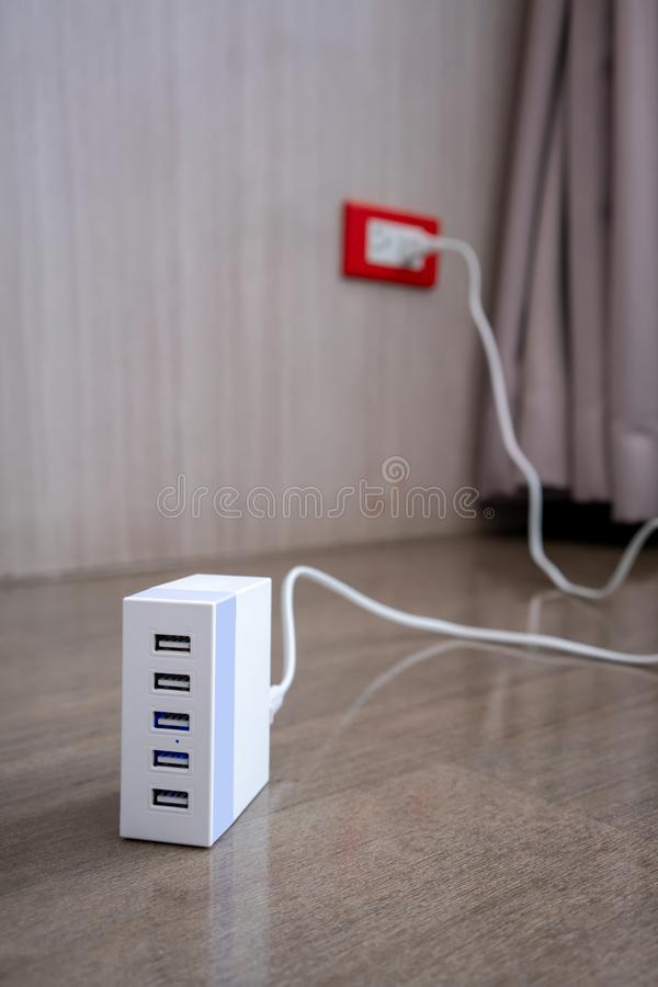 Multiport USB power adaptor charger for smart phone and tablet. On wooden floor royalty free stock photos