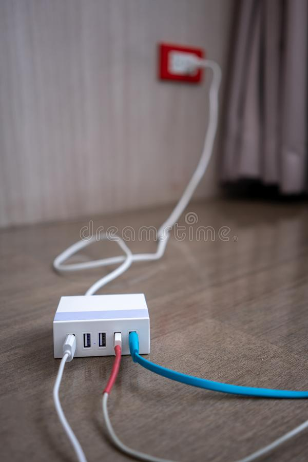 Multiport USB power adaptor charger for smart phone and tablet. On wooden floor stock photography