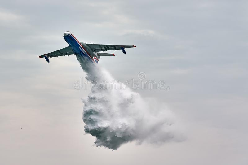 Multipurpose amphibian aircraft Beriev Be-200ES drops water. The aircraft demonstrates fire fighting over the Black Sea water royalty free stock photography
