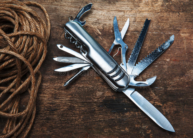 Multipurpose pocket knife on wooden background. Multipurpose pocket knife on wood royalty free stock photos