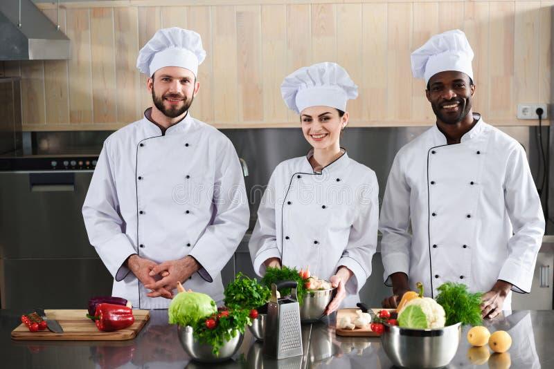 Multiraciaal chef-koksteam die door modern glimlachen stock afbeeldingen