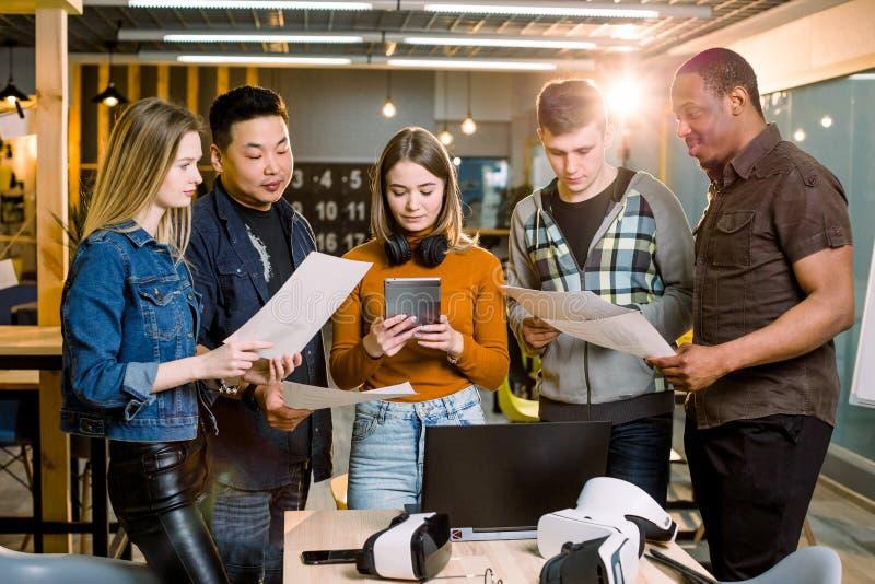 Multiraciaal commercieel team die tablet, laptop en virtuele werkelijkheidshoofdtelefoons in bureauvergadering met behulp van Ont royalty-vrije stock foto's
