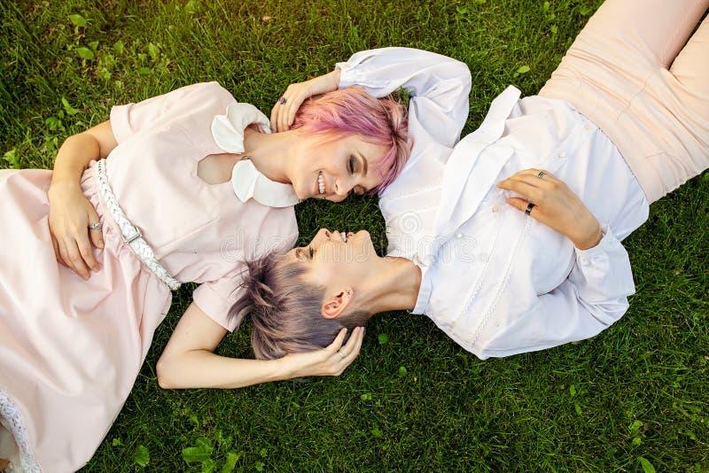 Multiraciaal lesbisch paar die op het gras liggen Zij zijn twee jonge vrouwen die bij park rusten Men is Kaukasisch en andere is  royalty-vrije stock fotografie