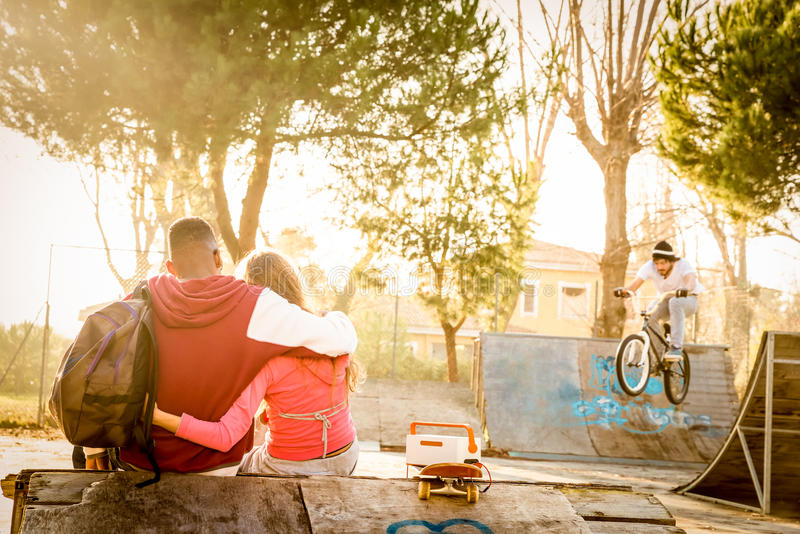 Multiraciaal liefdepaar bij vleetpark met muziek en fietser stock foto