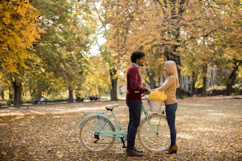 Multiraciaal paar met fiets in het de herfstpark royalty-vrije stock afbeeldingen