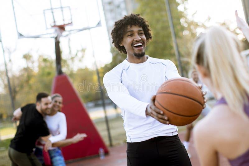 Multiraciaal paar speelbasketbal op openluchthof royalty-vrije stock afbeelding