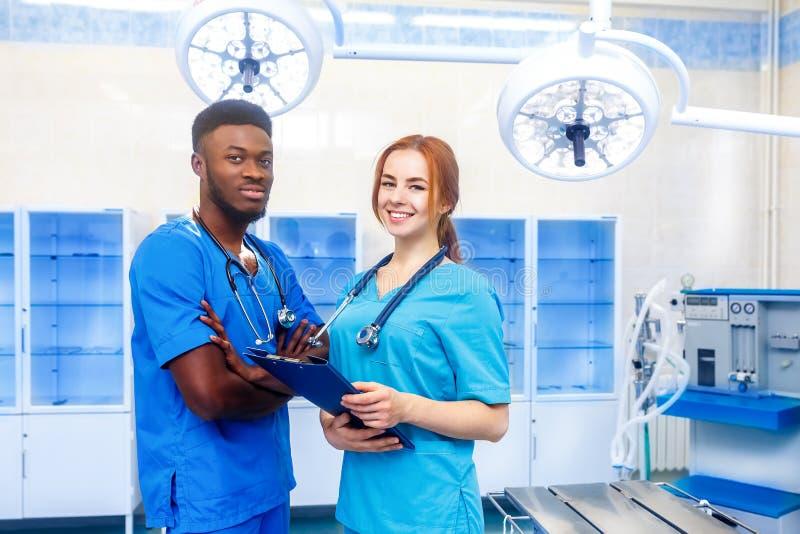 Multiraciaal team van twee jonge artsen in het ziekenhuis die zich in een werkende ruimte bevinden stock afbeeldingen
