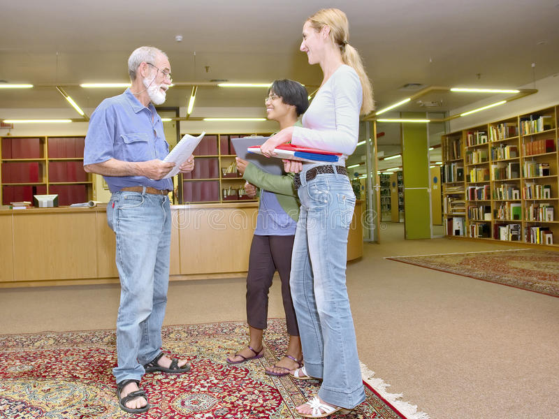 Multiraciale groep vriendschappelijke mensen die in bibliotheek babbelen stock fotografie