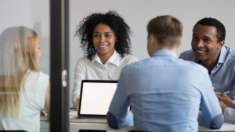 Multiraciaal zakenlui die in bestuurskamer zitten, die project, strategie bespreken stock foto