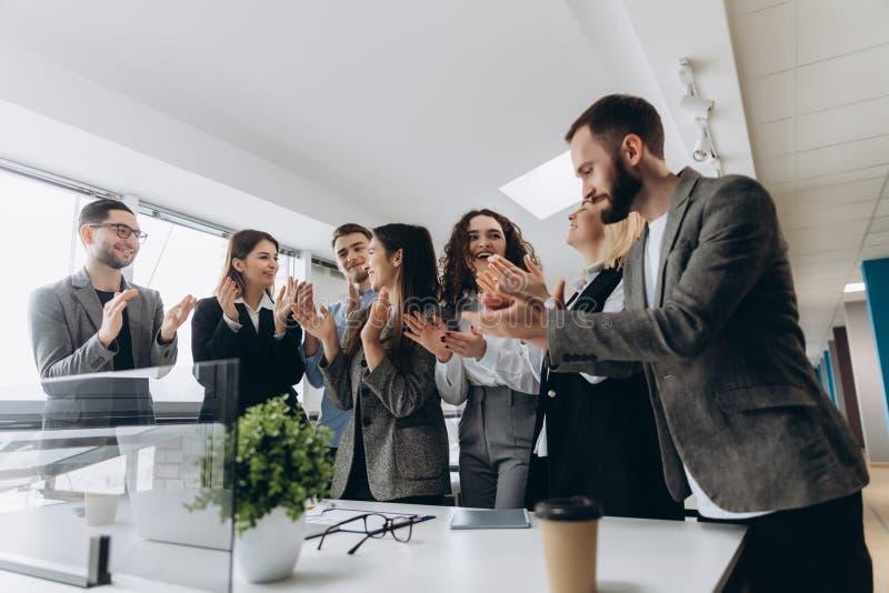 Multiracial группа в составе бизнесмены хлопая в ладоши для того чтобы поздравить их босса - команды деловой компании, аплодисмен стоковое фото rf