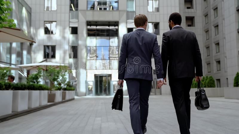 2 multiracial бизнесмена идя к офисному зданию, обсуждая взаимную работу стоковые фотографии rf