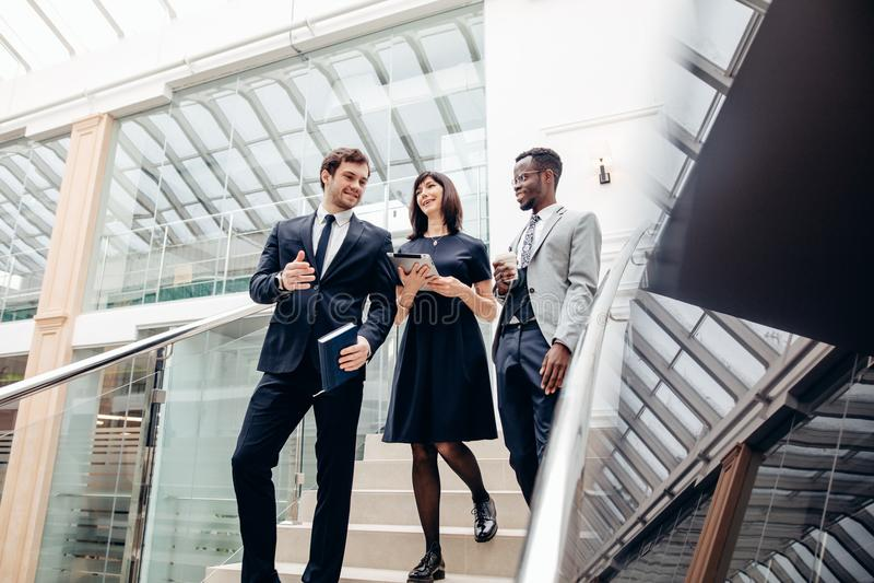 3 multiracial бизнесмены идя вниз на лестницы с цифровой таблеткой стоковая фотография rf