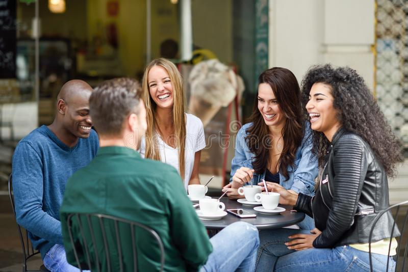 Multiracial группа в составе 5 друзей имея кофе совместно стоковое фото rf