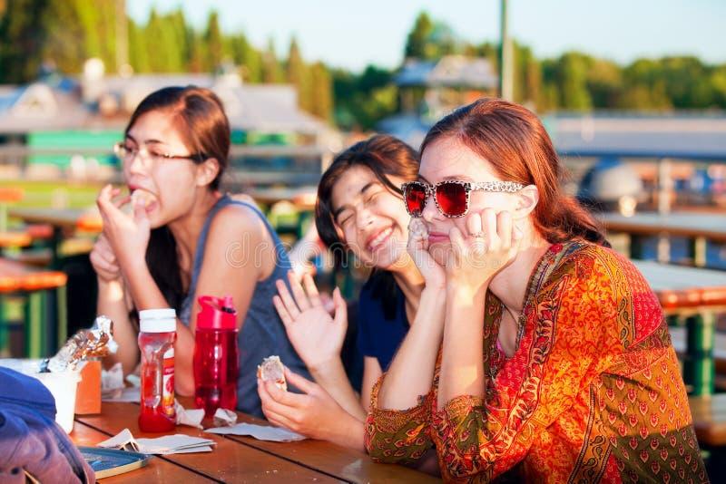 Multiracial группа в составе молодые женщины наслаждаясь временем совместно озером стоковая фотография rf