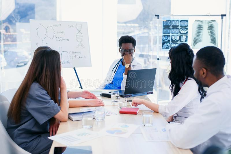 Multiracial группа в составе профессиональные врачи имеет встречу на конференц-зале в больнице Команда молодой стоковые изображения