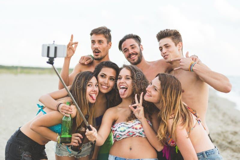 Multiracial группа в составе друзья принимая selfie на пляже стоковые фотографии rf