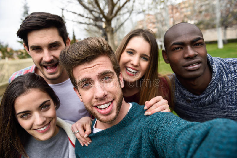Multiracial группа в составе друзья принимая selfie стоковая фотография