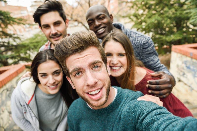 Multiracial группа в составе друзья принимая selfie стоковое фото
