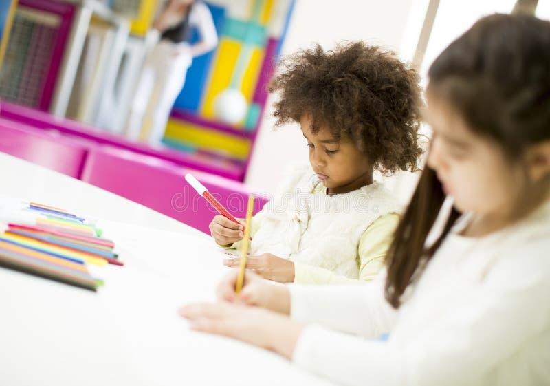 Multiracial дети рисуя в игровой стоковые изображения