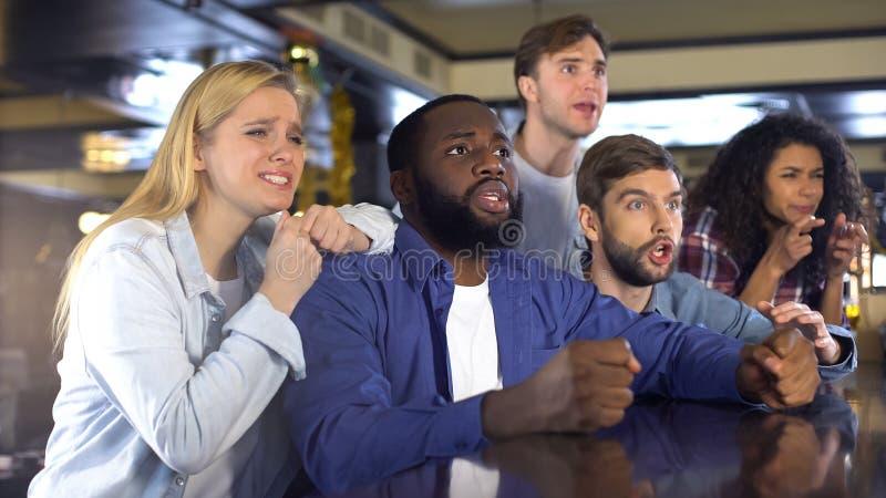 Multiracial друзья наблюдая спорт в баре, осадили о безнадежной игре, поражении стоковые изображения rf