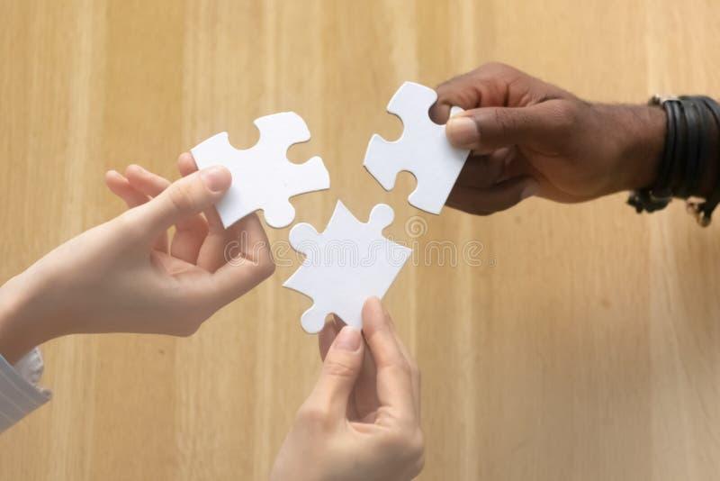 Multiracial женские мужские руки держа части головоломки выше таблица стоковая фотография rf