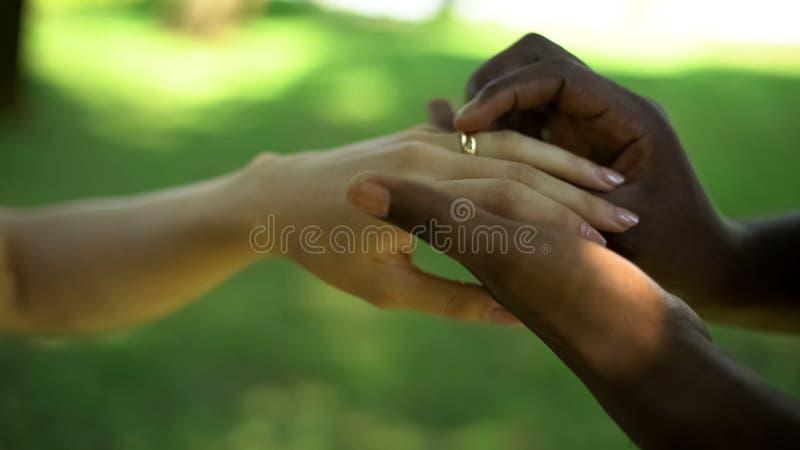 Multiracial замужество, мужская рука кладет золотое кольцо на невест палец, время свадьбы стоковое изображение rf