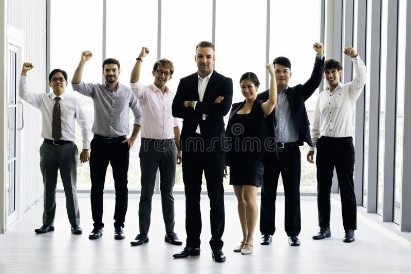 Multiracial команда дела празднуя победу в офисе стоковые фото