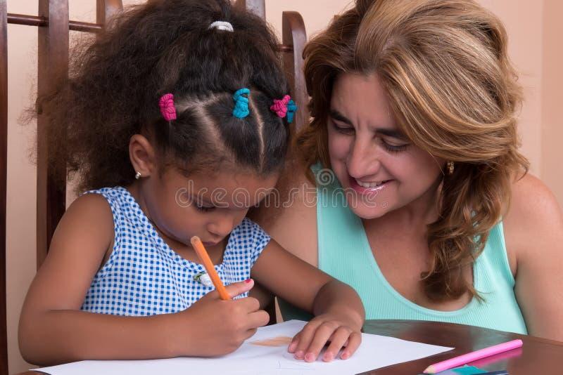 Multiracial малая девушка и ее чертеж матери с карандашами цвета стоковые фотографии rf