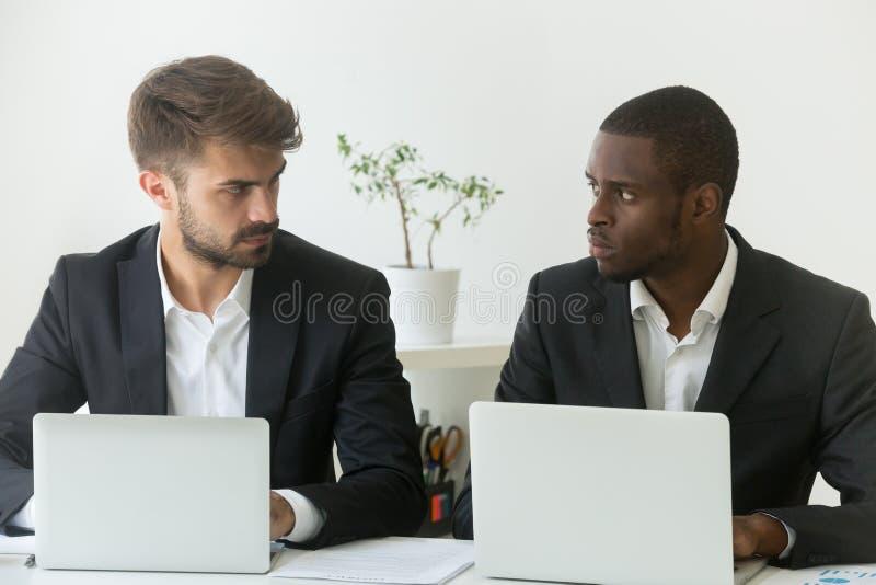 Multiracial офис соперничает смотреть один другого, соперничество на работе стоковая фотография rf