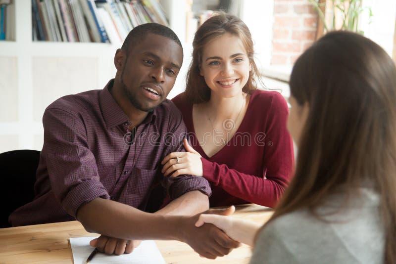Multiracial пары возбужденные с успешным приобретением дома общаются стоковое изображение