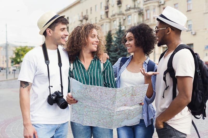 Multiracial пары обсуждая новые положения используя карту стоковое фото rf
