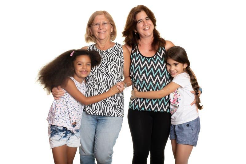 Multiracial семья - мама и бабушка обнимая их смешанных, который участвуют в гонке детей стоковое фото