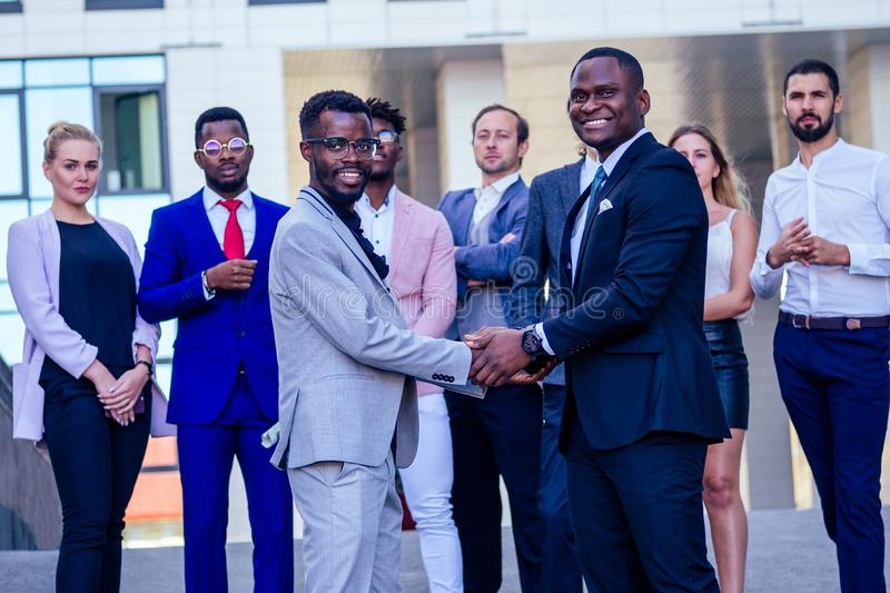 Multiracial african men handshaking at meeting and making deal shaking hands to businessman multinational and. Multiethnic corporate business people . Greeting royalty free stock photos