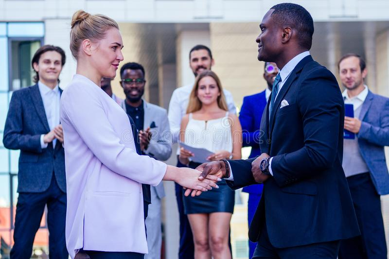 Multiracial african men handshaking at meeting and making deal shaking hands to white caucasian business woman. Multiracial african men handshaking at meeting royalty free stock photo