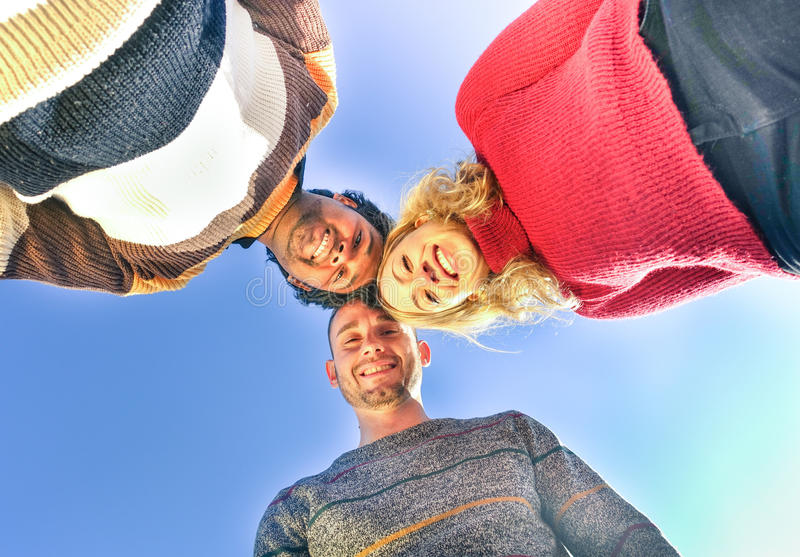 Multiracial best friends holding heads together looking down at stock photo
