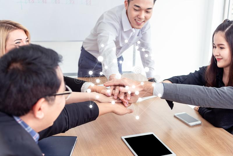 Multiracial business people collapse stacking hands over work table in modern meeting room.Teamwork join hands support together in stock images