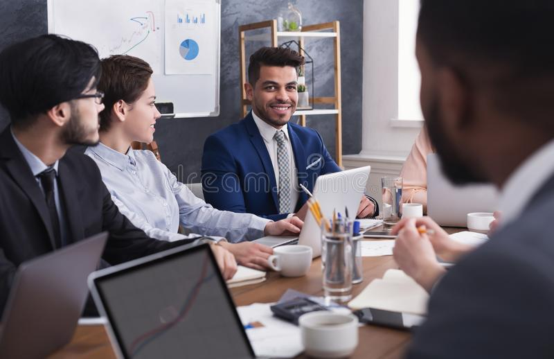 Multiracial business people discussing project at meeting stock photography