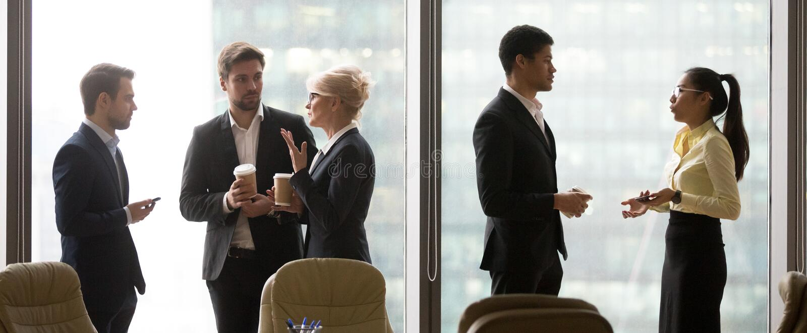 Multiracial, business people talking in break, standing near win. Multiracial, business people talking in break, drink coffee, standing near window. Asian and royalty free stock photography