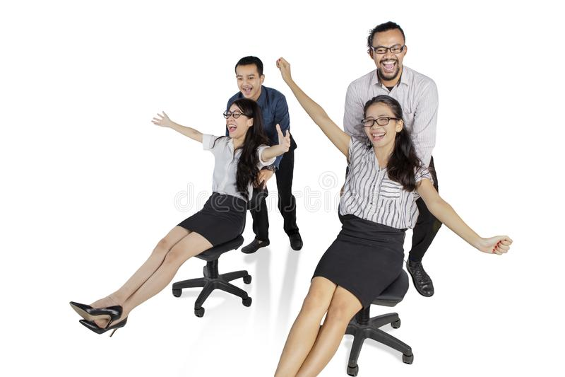 Multiracial business team racing on chairs royalty free stock photography