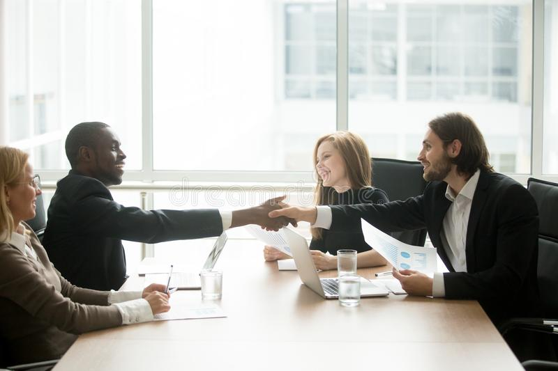 Multiracial businessmen in suits handshaking at executive team o royalty free stock images
